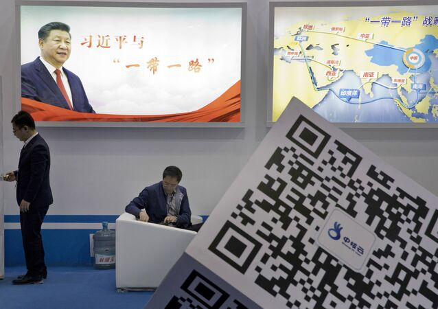 Visitors at a technology conference wait near illuminated boards highlighting Chinese President Xi Jinping's signature One Belt, One Road foreign policy plan in Beijing, China, Friday, April 28, 2017