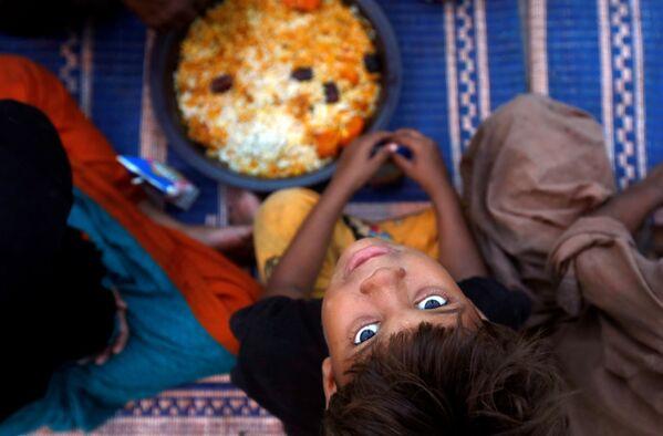 Un ragazzo aspetta il cibo durante il Ramadan in Pakistan. - Sputnik Italia