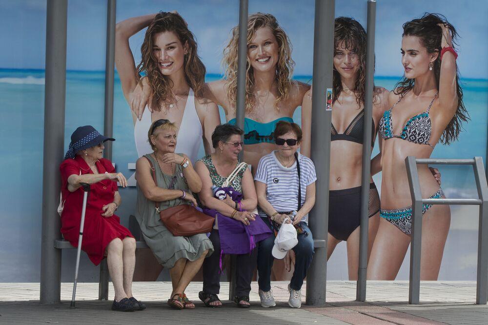 Donne anziane aspettano l'autobus alla fermata con l'immagine che raffigura costumi da bagno a Madrid, Spagna.