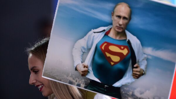 Un giornalista tiene un cartellino con l'immagine di Vladimir Putin prima della linea diretta con il presidente (foto d'archivio) - Sputnik Italia