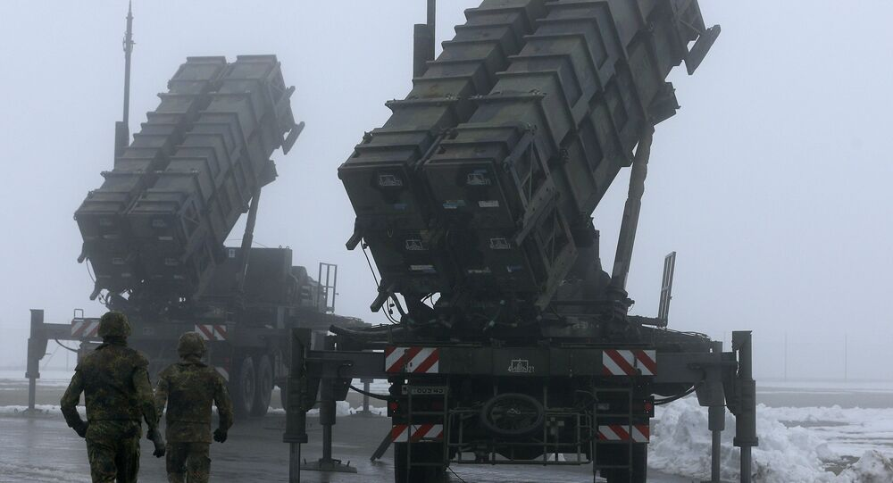 Two soldiers run toward Patriot antimissile systems