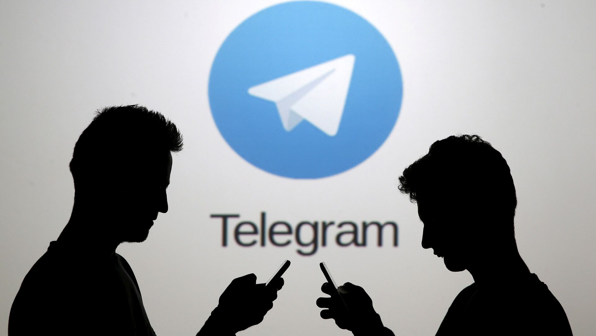 Men pose with smartphones in front of a screen showing the Telegram logo in this picture illustration November 18, 2015. - Sputnik Italia, 1920, 16.05.2021