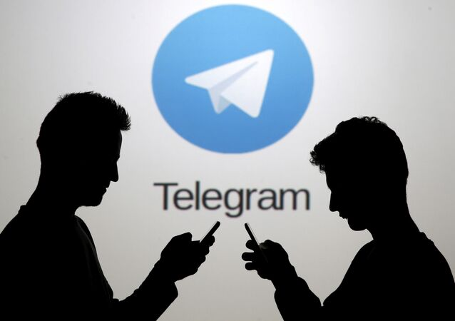 Men pose with smartphones in front of a screen showing the Telegram logo in this picture illustration November 18, 2015.