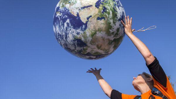 Девушка кидает шар в виде Земли - Sputnik Italia