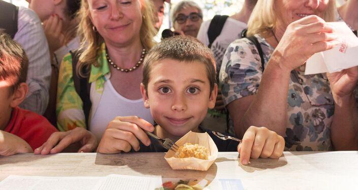 Un bambino prova un assaggio al padiglione russo di EXPO 2015