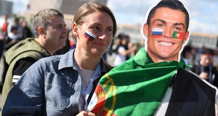 Una tifosa russa insieme ad un poster di Cristiano Ronaldo fuori dallo stadio Spartak di Mosca