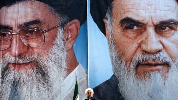 Iranian President Hassan Rouhani delivers a speech under portraits of Iran's supreme leader, Ayatollah Ali Khamenei (L) and Iran's founder of the Islamic Republic, Ayatollah Ruhollah Khomeini (R), on the eve of the 25th anniversary of the Islamic revolutionary leader Ayatollah Ruhollah Khomeini's death, at his mausoleum in a suburb of Tehran - Sputnik Italia