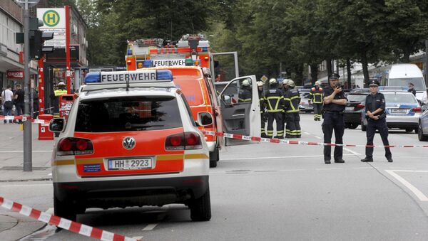 Police officers and fire engines stand in front of the supermarket in Hamburg, Germany, Friday, July 28, 2017, where a man with a knife fatally stabbed one person and wounded four others as he fled, police said - Sputnik Italia