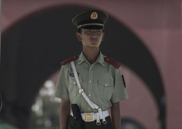 Un militare cinese vicino ad un ritratto di Mao Zedong