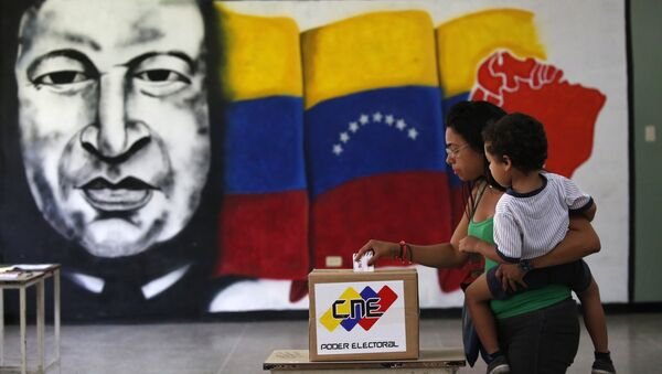 A  woman holds her infant as she casts her vote in front of a mural of the late Venezuelan President Hugo Chavez at a polling station during the Constituent Assembly election in Caracas, Venezuela, July 30, 2017. - Sputnik Italia