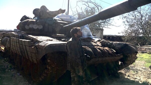Syrian Arab Army soldier stands near a T72 tank in the town of Al-Shaykh Maskin in the Daraa province liberated from terrorists - Sputnik Italia