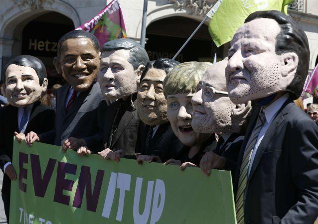 Gli attivisti con maschere che rappresentano le facce dei leader di G7