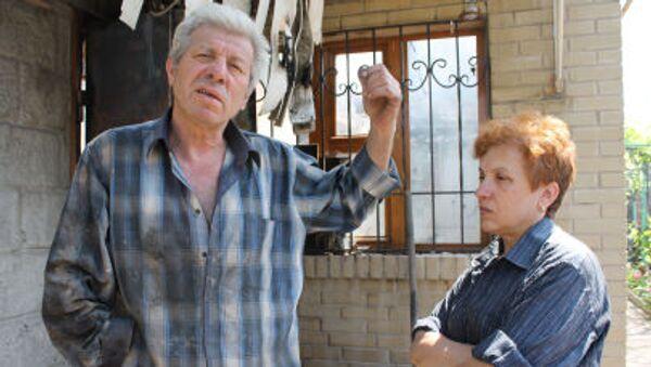 Abitanti locali davanti a una casa distrutta dal bombardamento del quartiere Oktjabrskij a Donetsk - Sputnik Italia