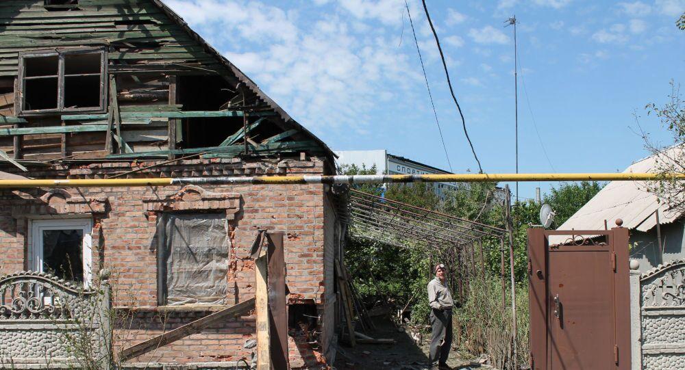 Un abitante locale nel cortile di una casa distrutta dal bombardamento del quartiere Oktjabrskij a Donetsk