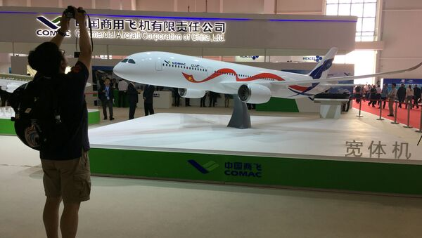 A man takes picture of the model of a widebody jet, which is planned to be developed by Commercial Aircraft Corporation of China (COMAC) and Russia's United Aircraft Corporation (UAC) at an air show, the China International Aviation and Aerospace Exhibition, in Zhuhai, Guangdong Province, China, November 2, 2016 - Sputnik Italia