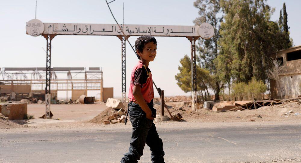 Un bambino cammina per le strade devastate di Raqqa