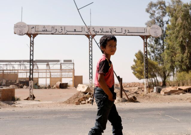 A boy walks past a sign which reads 'Islamic State in Iraq and Syria' as fighting continues between the Syrian Democratic Forces and Islamic State militants in Raqqa, Syria, August 20, 2017
