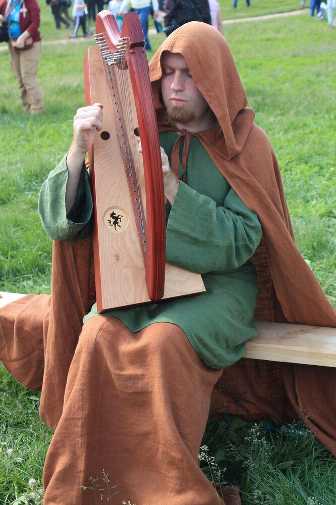 Участник фестиваля играет на древнеримском инструменте