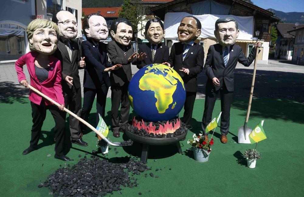 Manifestanti con le maschere dei leader del G7