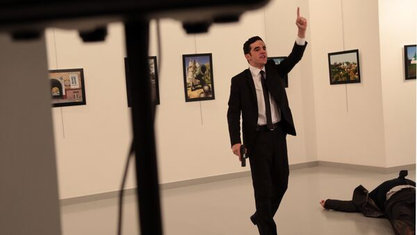 A man gestures near to Andrei Karlov on ground, the Russian Ambassador to Turkey at a photo gallery in Ankara, Turkey, Monday, Dec. 19, 2016 - Sputnik Italia