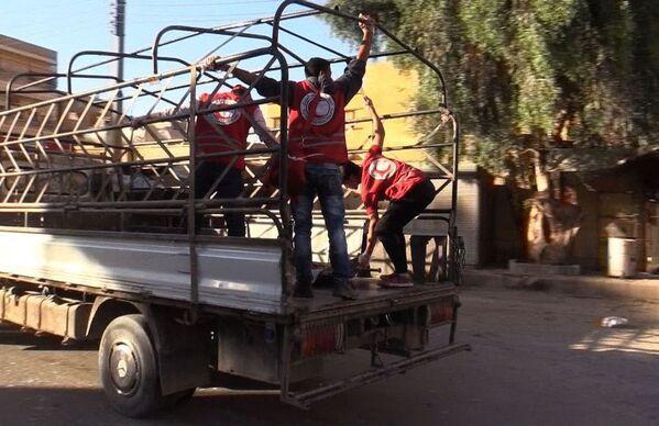 I collaboratori della Mezzaluna Rossa nel quartiere Al Qusur a Deir-ez-Zor dopo i bombardamenti. - Sputnik Italia