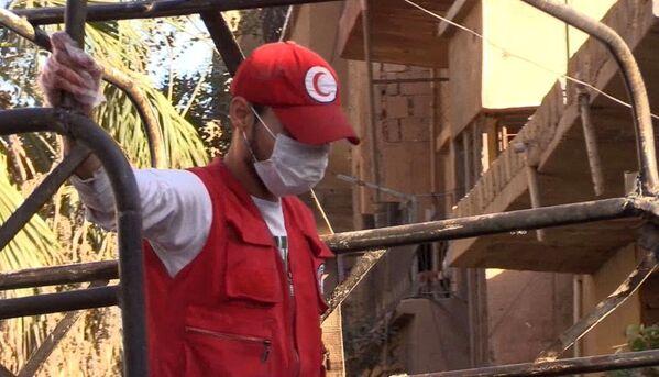 Un collaboratore della Mezzaluna Rossa nel quartiere Al Qusur a Deir-ez-Zor dopo i bombardamenti. - Sputnik Italia