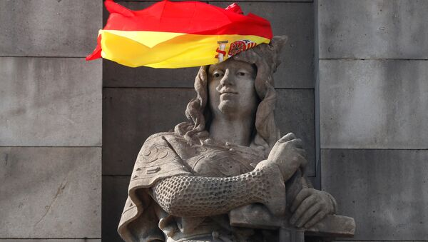 A Spanish flag hangs over the face of a figure representing one of the four realms of Spain on the statue to Columbus in Barcelona, Spain, October 11, 2017. - Sputnik Italia