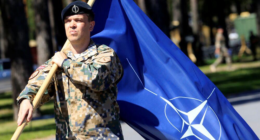 Militare lettone con la bandiera della NATO