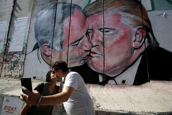 Turisti si fanno una foto vicino al graffiti che raffigura Trump che bacia il primo ministro israeliano Netanyahu. - Sputnik Italia