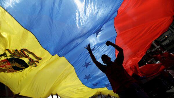 Pro-government supporters holding a Venezuela's flag attend a rally against U.S President Donald Trump in Caracas, Venezuela August 14, 2017 - Sputnik Italia