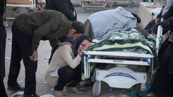 A woman reacts next to a dead body following an earthquake in Sarpol-e Zahab county in Kermanshah, Iran November 13, 2017 - Sputnik Italia