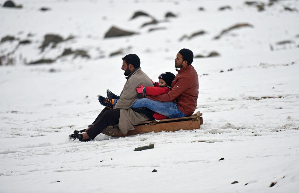 I kashmiri vanno in slitta dopo la prima nevicata nelle montagne nei pressi della città di Srinagar.