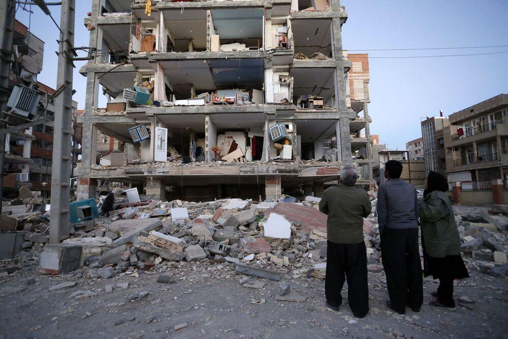 Gente guarda un edificio distrutto dal terremoto nella città di Sarpol-e-Zahab in Iran.