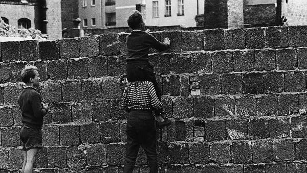 Un bambino sulle spalle di un altro bambino guarda oltre le mura che dividevano Berlino Ovest da Berlino Est - Sputnik Italia