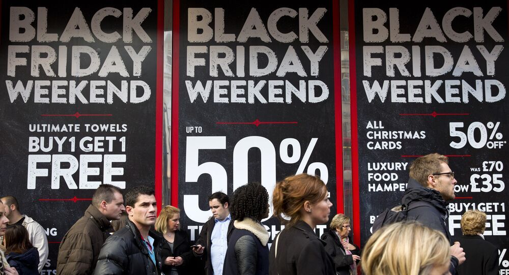 Shoppers are pictured walking past 'Black Friday' advertising in shop windows on Oxford Street in central London on November 28, 2014.