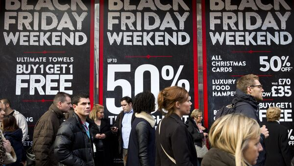 Shoppers are pictured walking past 'Black Friday' advertising in shop windows on Oxford Street in central London on November 28, 2014. - Sputnik Italia