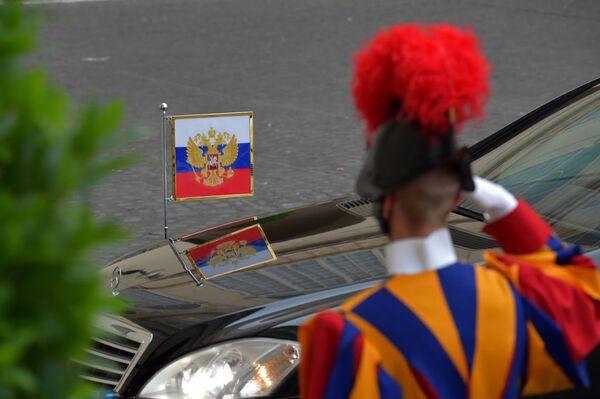 Una guardia svizzera saluta la partenza dell'auto di Putin. - Sputnik Italia