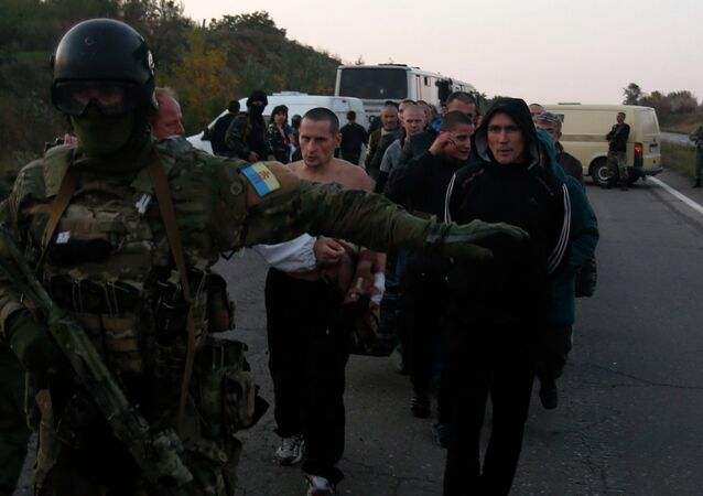 An Ukrainian soldier guards members of the Pro-Russian forces, who are prisoners-of-war, during prisoners exchange near the town of Donetsk, eastern Ukraine, Sunday, Sept. 28, 2014