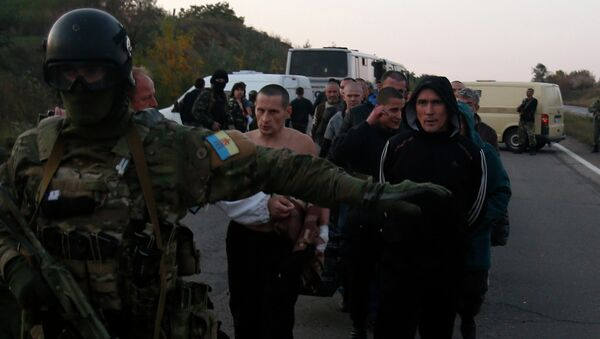 An Ukrainian soldier guards members of the Pro-Russian forces, who are prisoners-of-war, during prisoners exchange near the town of Donetsk, eastern Ukraine, Sunday, Sept. 28, 2014 - Sputnik Italia