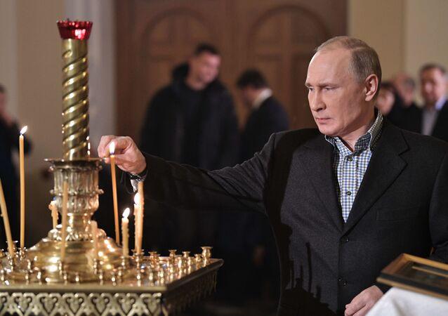 Il presidente russo Vladimir Putin durante la Messa di Natale presso la chiesa dei santi Simeone e Anna a San Pietroburgo.