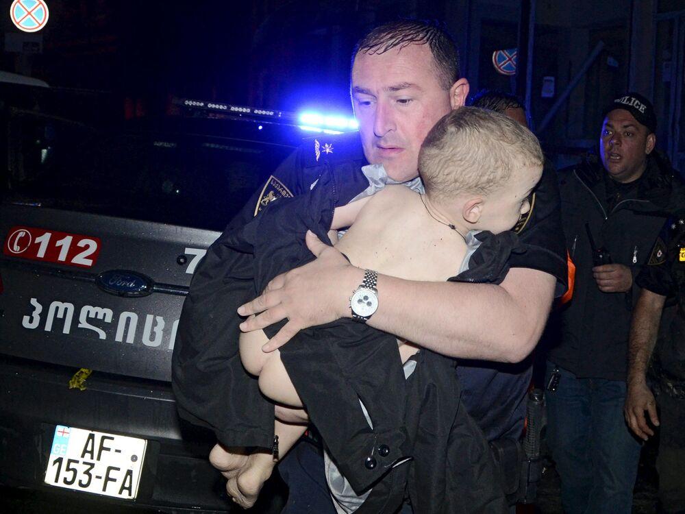 Un soccorritore evacua un bambino da una casa inondata a Tbilisi.