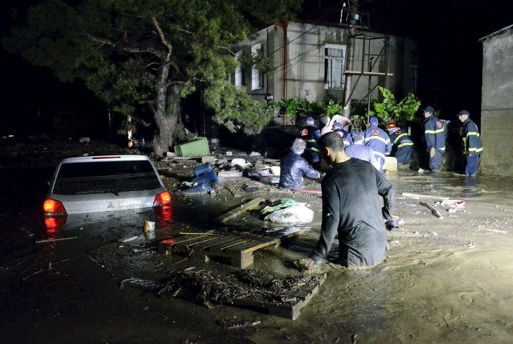 I soccorritori e gli abitanti sulle strade inondate a Tbilisi.