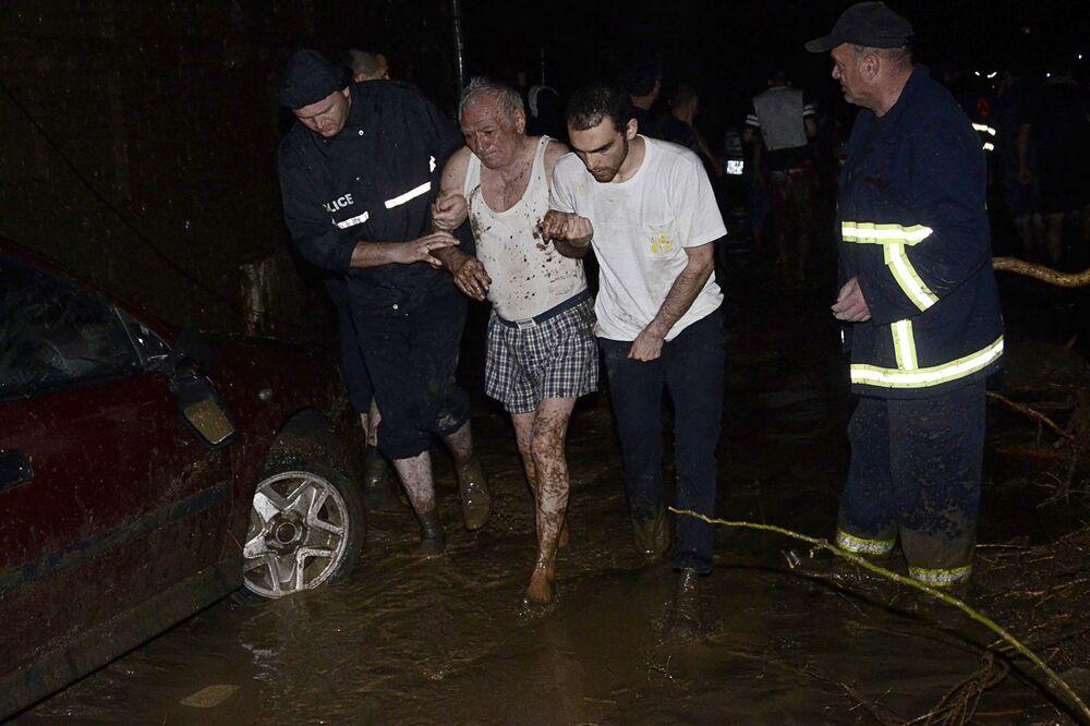 Un uomo viene soccorso dai pompieri dopo l'alluvione di Tbilisi.