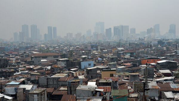 This general view shows informal settlers' homes (foreground) dwarped by highrise buildings in the background near the port of Manila - Sputnik Italia