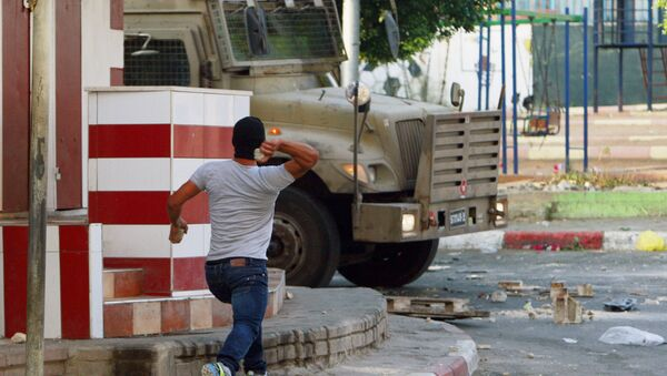 A Palestinian throws a stone toward an Israeli vehicle during clashes with Palestinians in an early morning operation in the West Bank city of Jenin, Wednesday, July 2, 2014. - Sputnik Italia