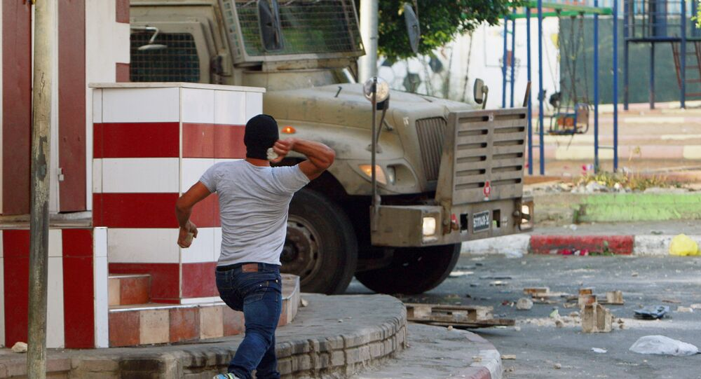 A Palestinian throws a stone toward an Israeli vehicle during clashes with Palestinians in an early morning operation in the West Bank city of Jenin, Wednesday, July 2, 2014.