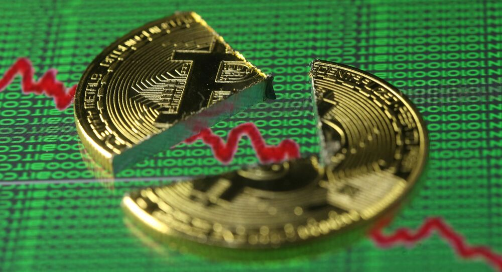 Broken representation of the Bitcoin virtual currency, placed on a monitor that displays stock graph and binary codes, are seen in this illustration picture, December 21, 2017
