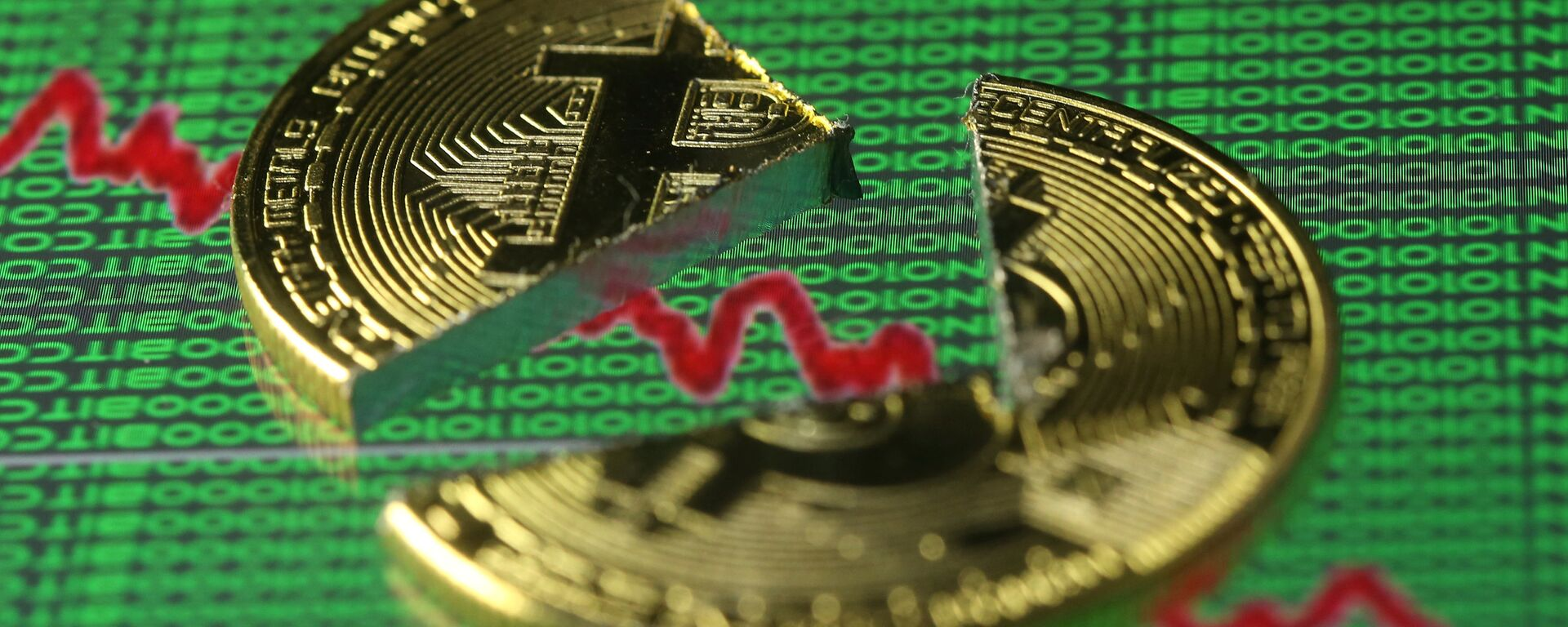 Broken representation of the Bitcoin virtual currency, placed on a monitor that displays stock graph and binary codes, are seen in this illustration picture, December 21, 2017 - Sputnik Italia, 1920, 01.07.2021