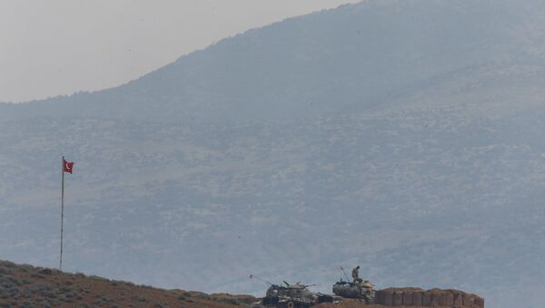 Soldiers man a Turkish Army artillery position, as seen from the outskirts of the village of Sugedigi, Turkey, near the border with Syria, background - Sputnik Italia
