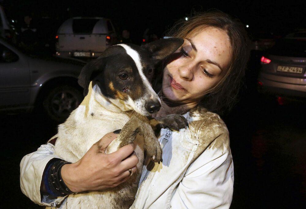 Una donna porta in salvo il suo cane durante l'alluvione a Tbilisi.
